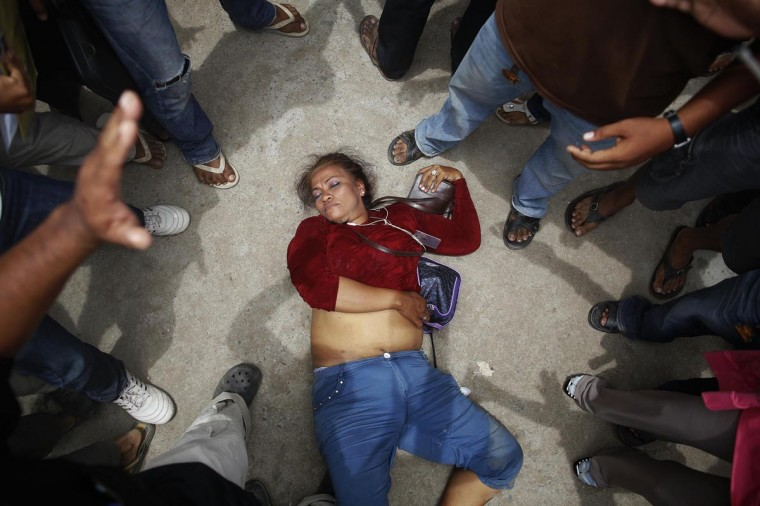 An election committee official lies unconscious after an angry mob surrounded her in a protest against alleged election irregularities at a polling station in Phnom Penh July 28, 2013. Cambodians voted on Sunday in an election likely to hand another five years in power to Asia's longest-serving prime minister, Hun Sen, but an energized opposition says there have been irregularities and it will continue to fight for true democracy. (Damir Sagolj/Reuters)