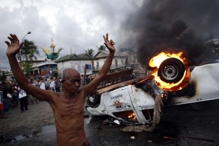 A man raises his hands in front of a burning police vehicle following a brief clash at the end of election day in Phnom Penh July 28, 2013. Security was tightened in Cambodia's capital, Phnom Penh, on Sunday after polling ended in a general election. (Damir Sagolj/Reuters)
