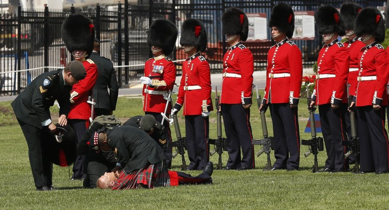 A member of the Ceremonial Guard is assisted after fainting during a ceremony marking the change of command of the Canadian Army on Parliament Hill in Ottawa. (Chris Wattie/Reuters photo)