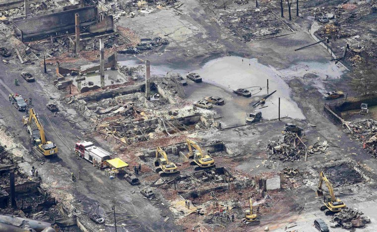 Workers and firefighters work around the remains of downtown Lac Megantic July 8, 2013. (Mathieu Belanger/Reuters)