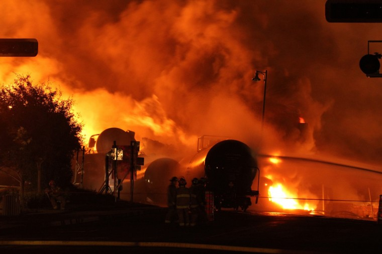 First responders fight burning trains after a train derailment and explosion in Lac-Megantic, Quebec early July 6, 2013. (Transportation Safety Board of Canada via Reuters)