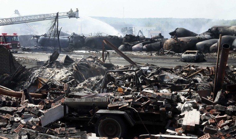 The remains of a home lie in rubble as firefighters continue working on the scene of a train derailment in Lac Megantic, Quebec, July 7, 2013. (Christinne Muschi/Reuters)