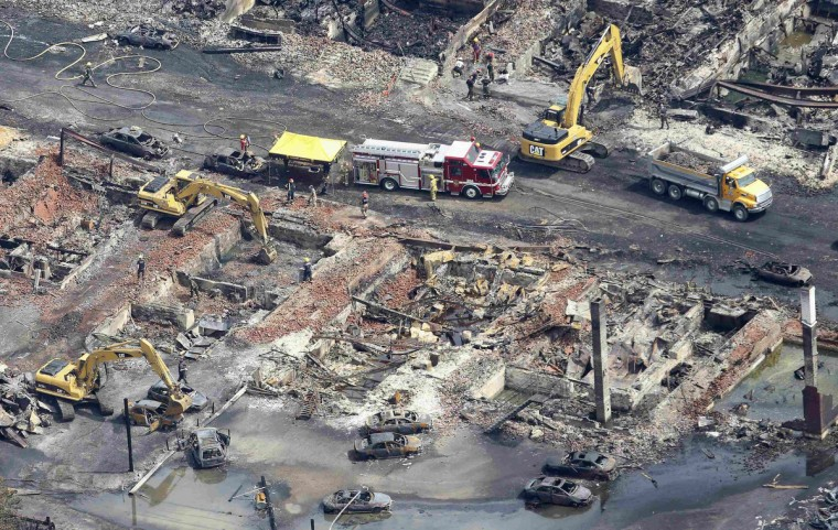 Workers and firefighters work on the remains of downtown Lac Megantic July 8, 2013. (Mathieu Belanger/Reuters)