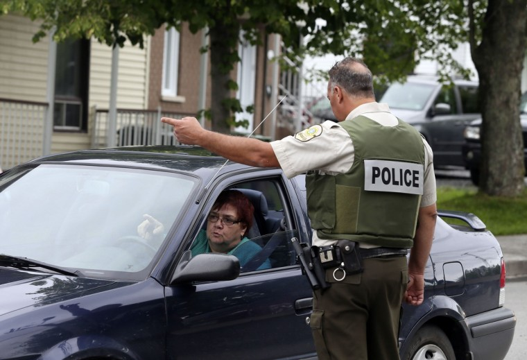 Police redirect residents away from their homes within the evacuation zone of the town of Lac Megantic, Quebec, July 8, 2013. (Christinne Muschi/Reuters)