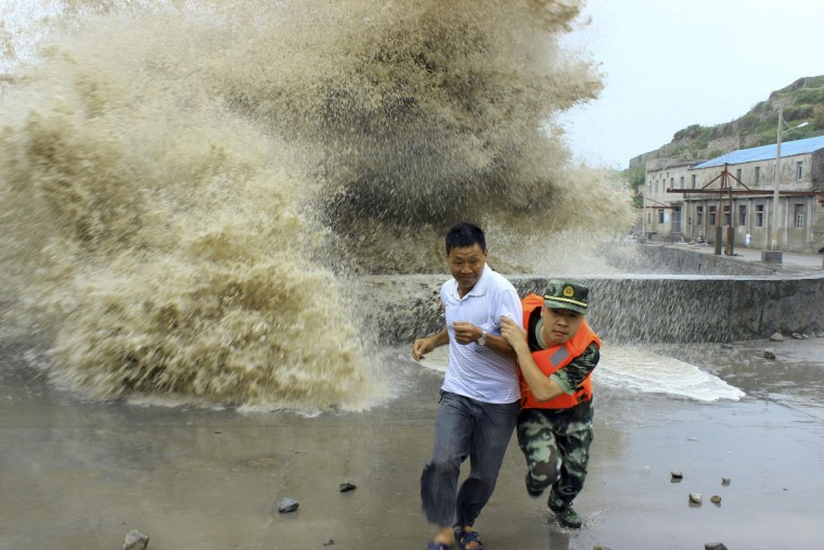 A frontier soldier helps a man move away from waves ahead of Typhoon Soulik in Wenzhou, Zhejiang province, July 13, 2013. China braced on Friday for the impact of Typhoon Soulik as the toll of dead and missing from torrential rain across a broad swathe of China climbed beyond 200. (Reuters/China Daily)