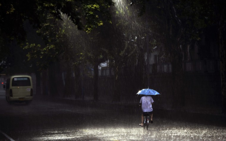 A man holds an umbrella as he rides along a street during a heavy rain in Jinan, Shandong province, China. (Stringer/Reuters photo)