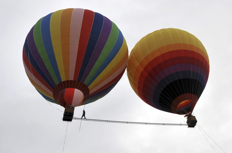 Aisikaier Wubulikasimu, 40-year-old Uighur acrobat, walks on a 18m long (59 ft), 50 mm wide (2 inch) tightrope strung between two hot air balloons, in Shilin county, Yunnan province. Wubulikasimu has previous broken two Guinness World Record for the fastest tightrope walk over 100m in 2009 and the steepest tightrope walk in 2011. (Reuters)