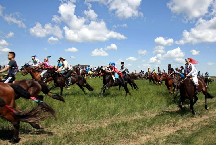 Herdsmen ride during a horse race in Xilin Gol League, in China's Inner Mongolia Autonomous Region, July 16, 2013. The annual two-day event has drawn around 1,000 participants from all over the Inner Mongolian region this year. (Jacky Chen/Reuters)