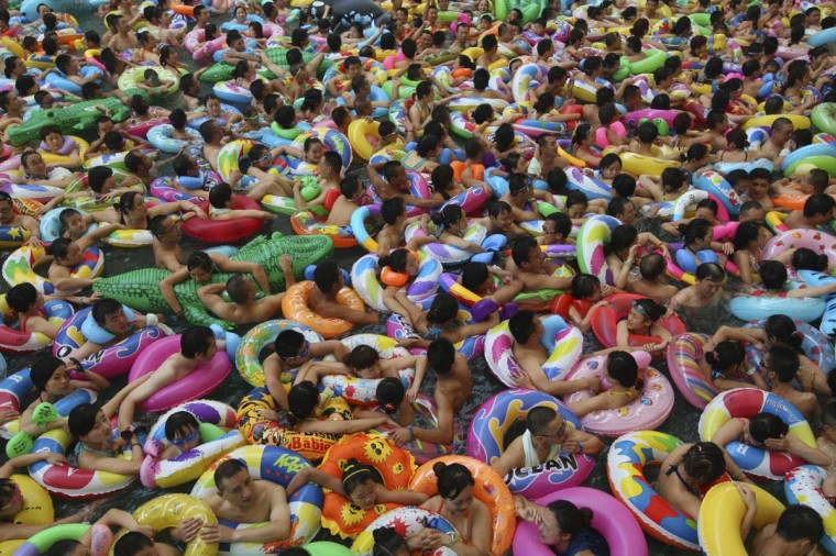 Visitors crowd an artificial wave pool at a tourist resort to escape the summer heat in Daying county of Suining, Sichuan province, July 27, 2013. (China Daily/Reuters)