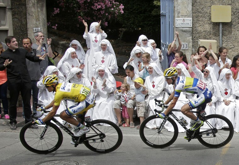 Race leader yellow jersey holder Orica Greenedge team rider Simon Gerrans of Australia cycles past Sisters of the Consolation congregation during the 228.5 km fifth stage of the centenary Tour de France cycling race from Cagnes-Sur-Mer to Marseille. (Jacky Naegelen/Reuters)