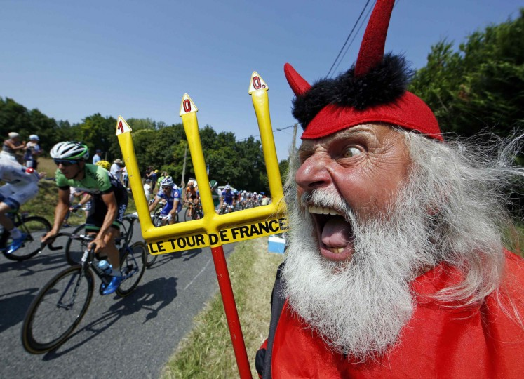 The pack of riders makes its way past Didi Senft, a cycling enthusiast better known as 'El Diablo' (The Devil), during the twelfth 218km stage of the centenary Tour de France cycling race from Fougeres to Tours. (Eric Gaillard/Reuters)