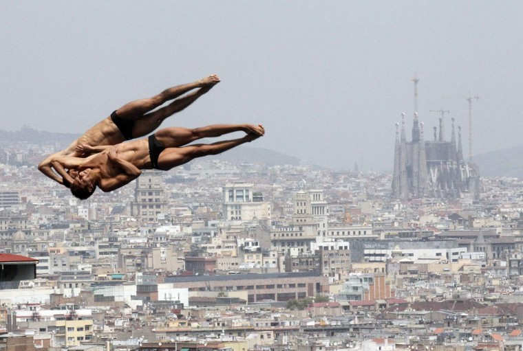 Mexico's Ivan Garcia (R) and German Sanchez perform a dive during a practice for the men's synchronized 10m platform event with a backdrop of the Sagrada Familia cathedral at the Montjuic municipal pool in Barcelona prior to the World Swimming Championships in Barcelona, July 17, 2013. The World Swimming Championships will take place July 20 to August 4. (Albert Gea/Reuters)