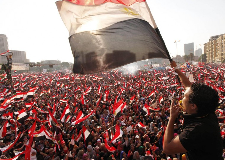 """Protesters against Egyptian President Mohamed Mursi wave national flags in Tahrir Square in Cairo July 3, 2013. The Egyptian president's national security adviser said on Wednesday that a """"military coup"""" was under way and army and police violence was expected to remove pro-Mursi demonstrators. (Mohamed Abd El Ghany/Reuters)"""