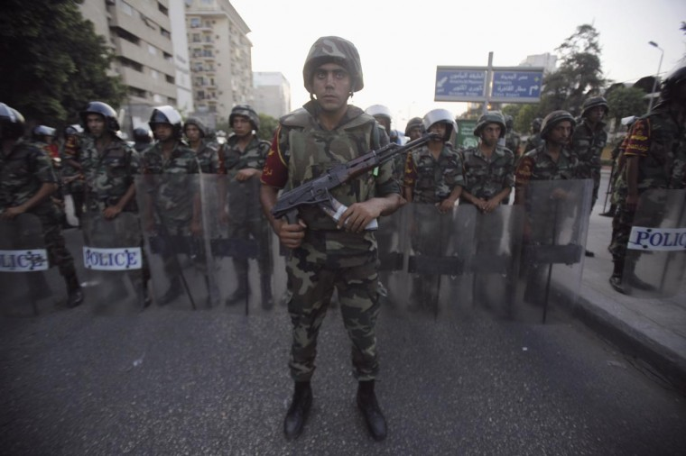 Army soldiers stand guard in front of protesters who are against Egyptian President Mohamed Mursi, near the Republican Guard headquarters in Cairo July 3, 2013. (Amr Abdallah Dalsh/Reuters)