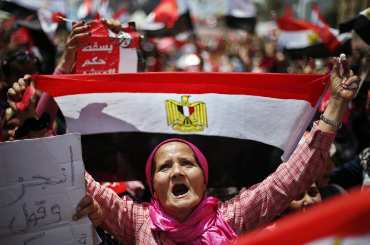 A protester, opposing Egyptian President Mohamed Mursi, holds up Egypt's flag during a protest demanding that Mursi resign at Tahrir Square in Cairo July 2, 2013. (Suhaib Salem/Reuters)