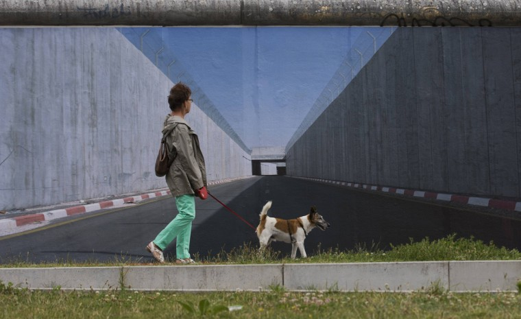 A woman walks past a picture showing a border fortification in the West Bank by German photographer Kai Wiedenhoefer at the former Berlin Wall in Berlin. Wiedenhoefer's Wall on Wall project consists of panoramic pictures of eight border walls that separate people in different parts of the world. The pictures are currently displayed as 9x3 metre prints that Wiedenhoefer has pasted onto the longest remaining stretch of the former Berlin Wall border fortification. (Thomas Peter/Reuters)