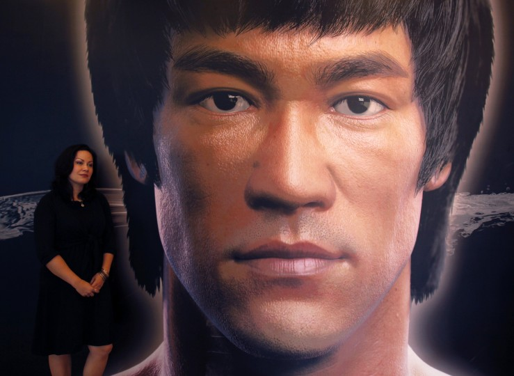 Shannon Lee, daughter of the late Kung Fu legend Bruce Lee, poses beside a portrait of her father at the Hong Kong Heritage Museum, before the start of a five-year exhibition on Lee. Late kung fu superstar Bruce Lee may be an international icon, but he is still not the complete local hero in Hong Kong. Fans are marking his death 40 years ago this weekend with art gallery shows, exhibitions and even street graffiti but some people are urging Hong Kong's government to do more to honor the former British colony's biggest star. (Bobby Yip/Reuters photo)