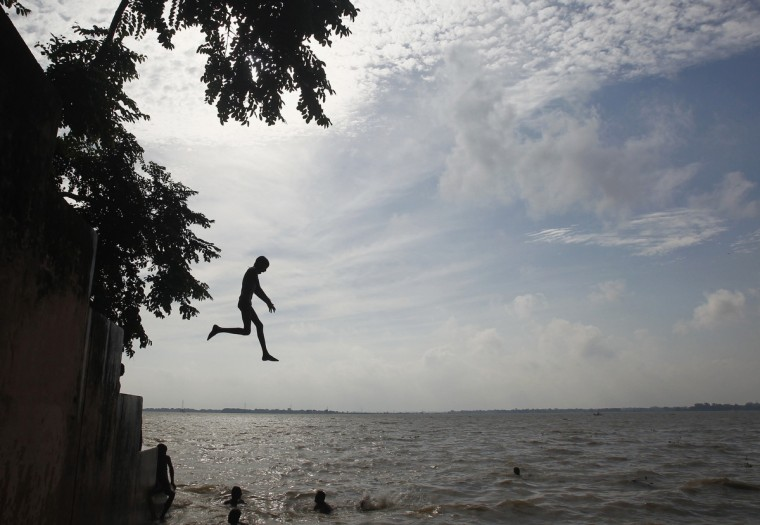 A boy jumps into waters of the river Ganges to cool himself in the northern Indian city of Allahabad. (Jitendra Prakash/Reuters)