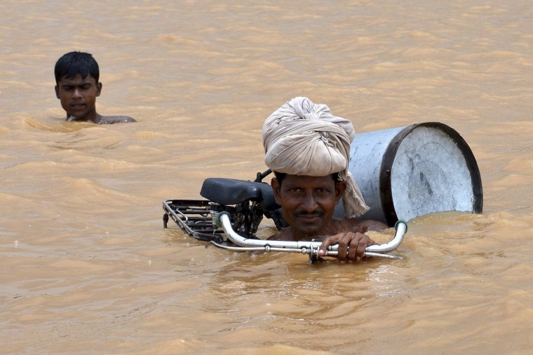 A flood-affected man with his bicycle moves to a safer place after the rise in the water levels of the river Ganges at Maner in the eastern Indian state of Bihar. (Krishna Murari Kishan/Reuters)