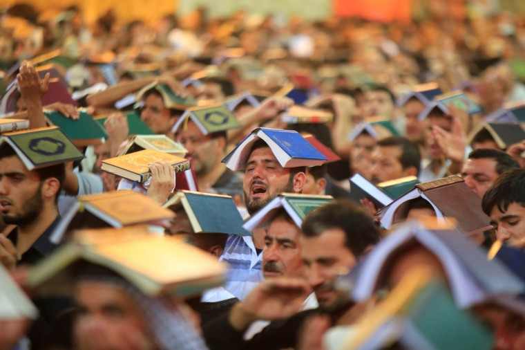 Shi'ite people place copies of the Koran on their heads during a ceremony marking the death anniversary of Imam Ali at his shrine in the holy city of Najaf, about 160 km (100 miles) south of Baghdad. Imam Ali, the son-in-law of Prophet Mohammad, was wounded in the head during a battle and died after two days in 661 AD in Najaf. (Ahmad Mousa/Reuters)