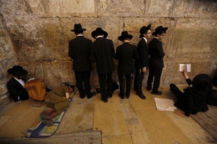 An Israeli soldier sleeps as ultra-Orthodox Jewish youths pray on Tisha B'Av at the Western Wall, Judaism's holiest prayer site, in Jerusalem's Old City July 16, 2013. Tisha B'Av, a day of fasting and lament, is traditionally the date in the Jewish calendar on which the First and Second Temples were destroyed, respectively in the sixth century B.C. by the Babylonians and the first century A.D. by the Romans. (Baz Ratner/Reuters)