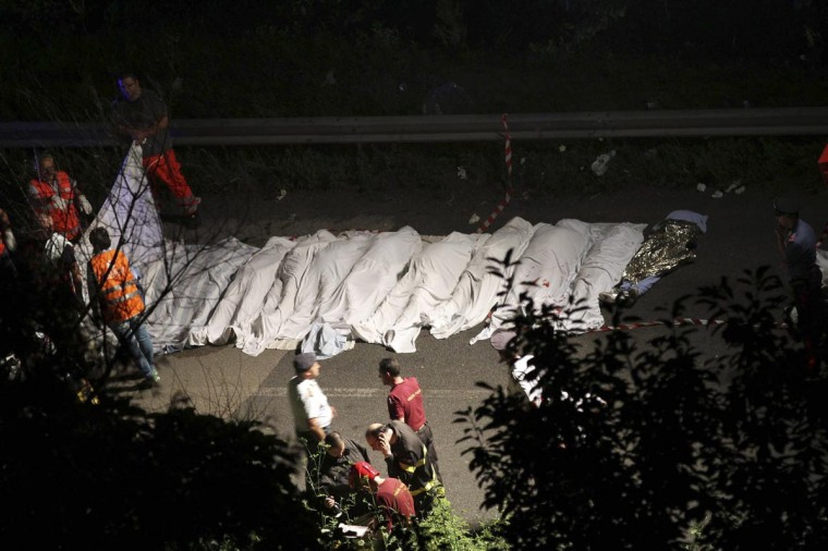 Bodies of victims are lined up after a coach crash near the southern town of Avellino July 28, 2013. At least 24 people died on Sunday after the bus plunged more than 15 meters off a viaduct in southern Italy, a spokesman for the fire service said. (Ansa/Cesare Abbate/Reuters)