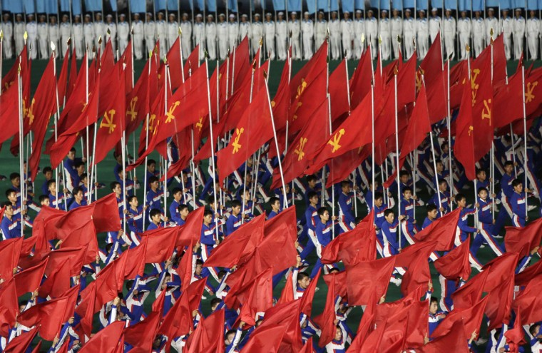 """North Koreans holding flags of Workers' Party perform during a mass gymnastic and artistic performance """"Arirang"""", in Pyongyang July 26, 2013, as part of celebrations ahead of the 60th anniversary of the signing of a truce in the 1950-1953 Korean War. (Jason Lee/Reuters)"""