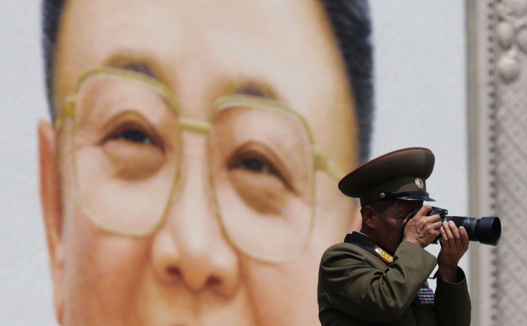 """A military officer takes a photograph in front of a giant portrait of late North Korean leader Kim Jong-il during a parade to mark the 60th anniversary of the signing of a truce in the 1950-1953 Korean War at Kim Il-sung Square, in Pyongyang July 27, 2013. North Korea celebrated the 60th anniversary of the Korean War truce on Saturday with a massive military parade trumpeting the revolutionary genius of three generations of leaders that gave it """"Victory in the Great Fatherland Liberation War."""" (Jason Lee/Reuters)"""