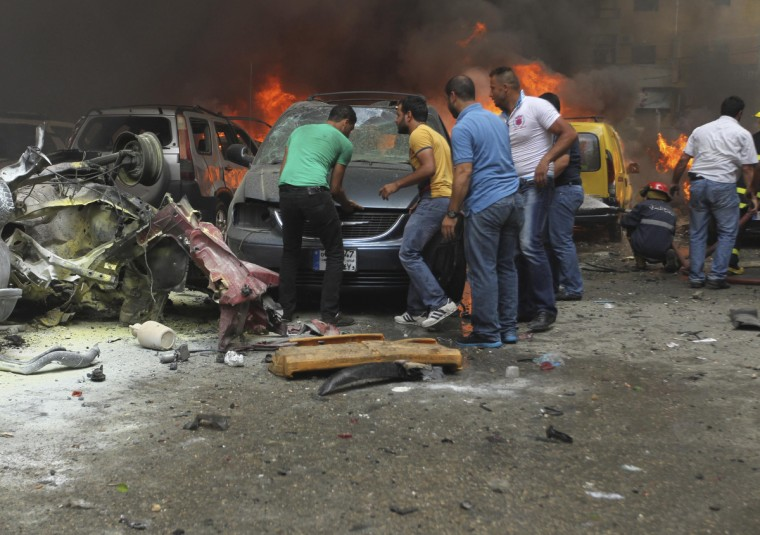 People gather at the site of an explosion in Beirut's southern suburbs. At least 18 people were wounded by a car bomb blast in Beirut's southern suburbs on Tuesday, a stronghold of the Lebanese Shi'ite Hezbollah militant group that has been fighting in Syria's civil war, security sources said. The sources were unable to confirm initial reports from medics at the scene that an unspecified number were killed in the massive blast. (Hasan Shaaban/Reuters)