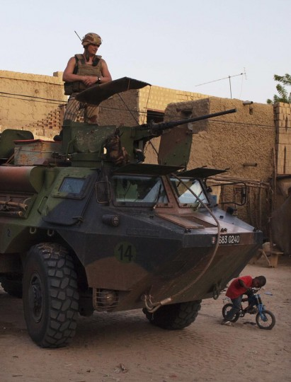 A boy on a bicycle peeks out from underneath a French soldier on patrol in an armored personnel carrier ahead of Mali's Sunday presidential election in Timbuktu, July 25, 2013. (Joe Penney/Reuters)