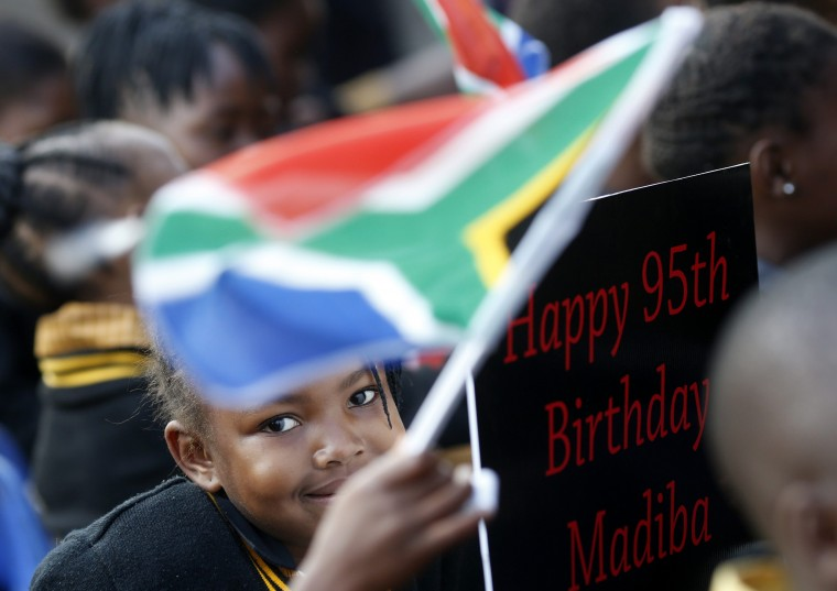 """Children hold placards as they gather to wish to former President Nelson Mandela happy birthday at a township school in Atteridgeville near Pretoria. Anti-apartheid hero Mandela is """"steadily improving"""", South Africa's government said on Thursday as the former president celebrated his 95th birthday in hospital amid tributes from around the country and the world. (Mike Hutchings/Reuters photo)"""