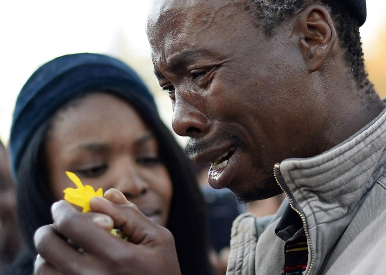A well wisher weeps as he pays his respects outside the Medi-Clinic Heart Hospital, where ailing former South African President Nelson Mandela is being treated, in Pretoria July 1, 2013. (Dylan Martinez/Reuters)