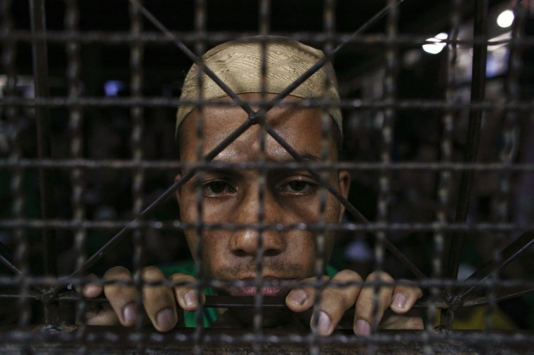 A Rohingya Muslim illegal immigrant looks out from the Immigration Detention Centre during the Muslim holy fasting month of Ramadan in Kanchanaburi province in this July 10, 2013 photo. (Athit Perewongmetha/Reuters)