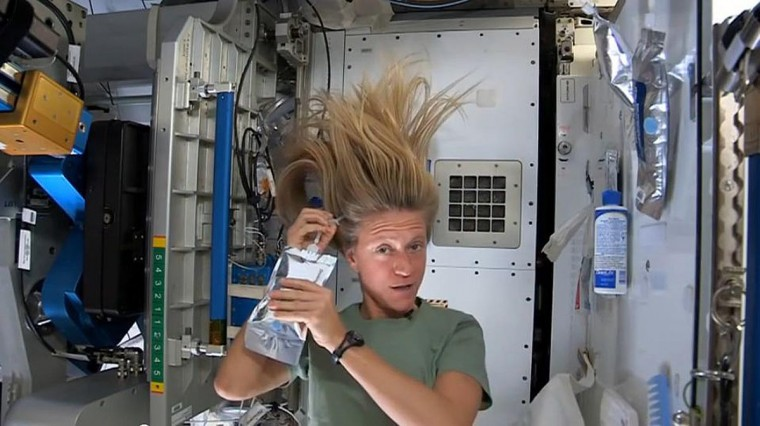 NASA astronaut Karen Nyberg, currently serving as part of Expedition 36 aboard the International Space Station, demonstrates how she washes her hair in zero gravity in this still image taken from NASA video released July 12, 2013. (NASA/Handout via Reuters