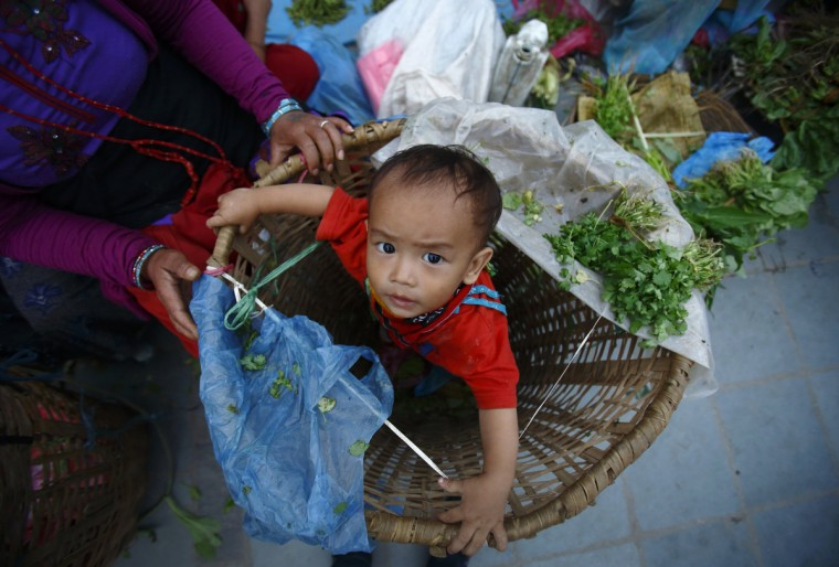 A boy looks up from inside a basket used to carry vegetables as his mother sells vegetables along the streets of Kathmandu. (Navesh Chitrakar/Reuters)