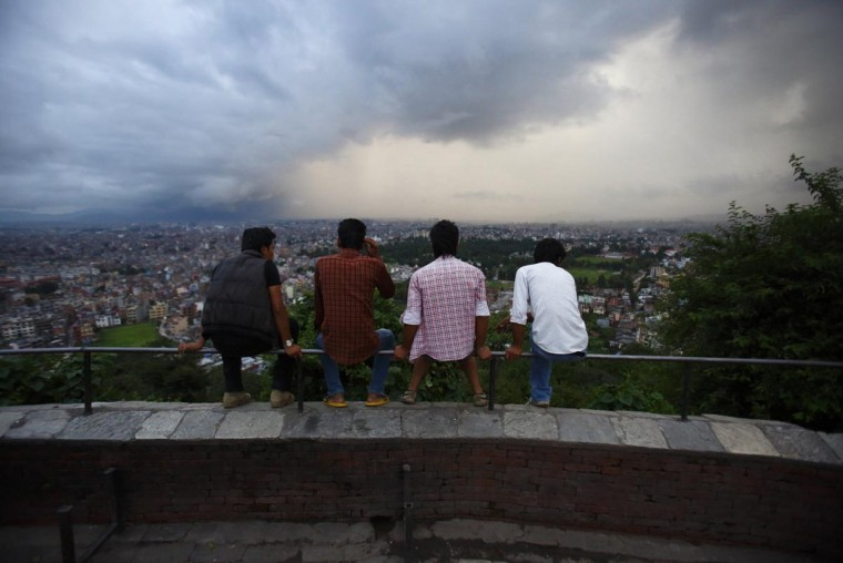 Nepalese youths watch as a monsoon cloud loomed over the Kathmandu skyline July 25, 2013. (Navesh Chitrakar/Reuters)