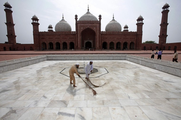 Workers clean the floor of the Badshahi Mosque ahead of the holy month of Ramadan in Lahore, July 9, 2013. (Mohsin Raza/Reuters)