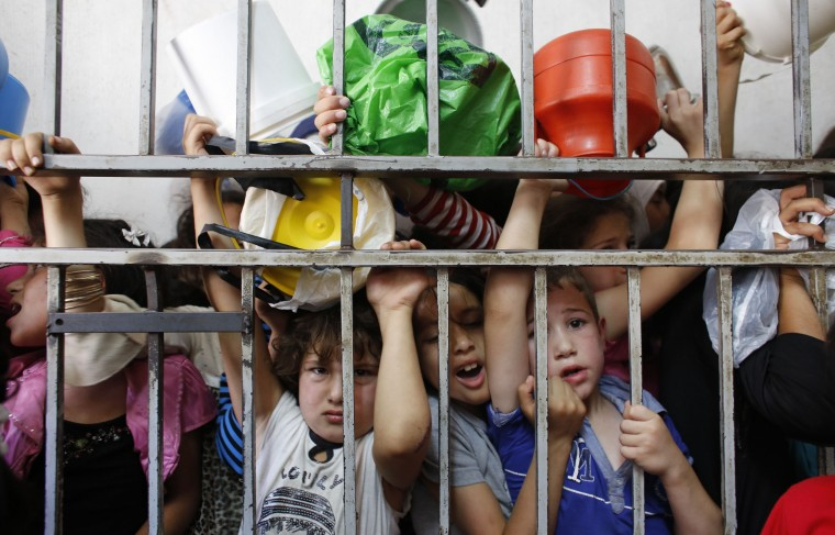 Palestinian children wait to receive food, donated by the Islamic endowment authority Islamic waqf, at a soup kitchen in the West Bank city of Hebron during the holy month of Ramadan. During Ramadan, there is an increase in demand for food, a manager at the soup kitchen said. (Ammar Awad/Reuters photo)