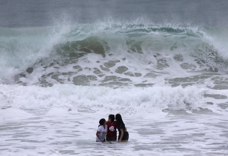 Catholic pilgrims embrace while standing in the sea as they await the arrival of Pope Francis on Copacabana beach in Rio de Janeiro July 25, 2013. Pope Francis is on the fourth day of his week-long visit for World Youth Day. (Ricardo Moraes/Reuters)