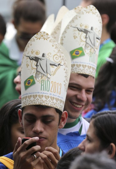 A faithful awaiting Pope Francis looks at his phone at the Quinta Boa Vista park where the Pope heard the confessions of youths attending the World Youth Day in Rio de Janeiro, July 26, 2013. Pope Francis on Thursday issued the first social manifesto of his young pontificate, telling slum dwellers in Brazil that the world's rich must do much more to wipe out vast inequalities between the haves and the have-nots. (Paulo Whitaker/Reuters)