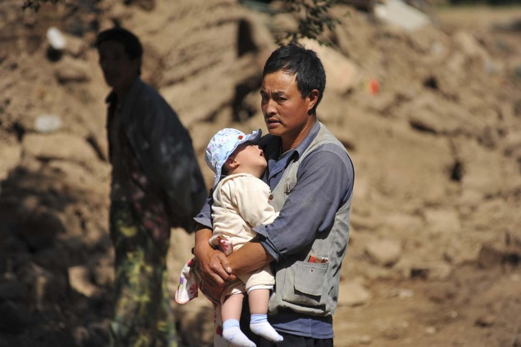 A man holds a baby after a 6.6 magnitude earthquake in Minxian county, Dingxi, Gansu province, July 22, 2013. The earthquake killed at least 89 people with hundreds injured for many homes in the affected areas collapsed, state media reported on Monday. (Stringer/Reuters)