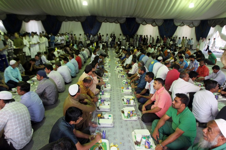 Laborers sit down before their first iftar, or breaking-fast, meal during the Muslim fasting month of Ramadan at an iftar tent in Riyadh July 10, 2013. (Faisal Al Nasser/Reuters)
