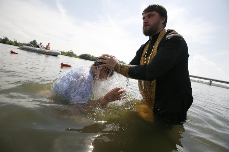 An Orthodox priest baptizes a woman in the Chulym river during a ceremony to mark the adoption of Christianity in Russia, outside Nazarovo town, 124 miles west of the Siberian city of Krasnoyarsk, July 28, 2013. In 2013, Russia officially celebrated the 1,025th anniversary of the Christianization of Kievan Rus, marking its conversion to Christianity in 988. (Ilya Naymushin/Reuters)