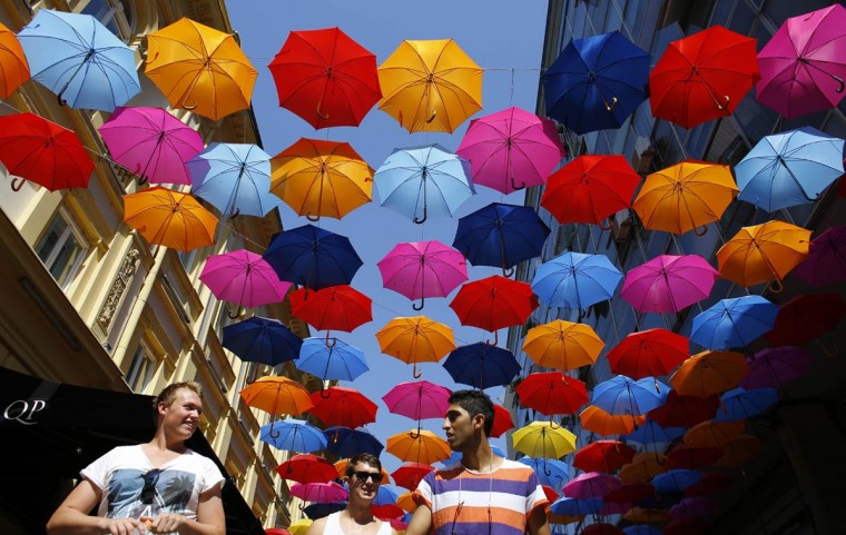 People walk past underneath an umbrella canopy in downtown Belgrade July 29, 2013. Temperatures in Serbia have risen up to 104 degrees Fahrenheit, according to official meteorological data. (Marko Djurica/Reuters)