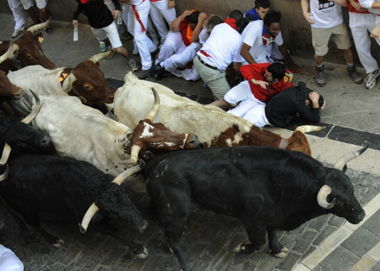 Runners fall next to Valdefresno fighting bulls on Santo Domingo hill during the third running of the bulls of the San Fermin festival in Pamplona. (Eloy Alonso/Reuters photo)