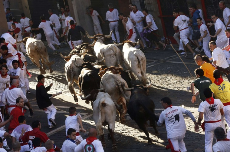 Runners sprint alongside Dolores Aguirre Ybarra fighting bulls during the second running of the bulls of the San Fermin festival in Pamplona. (Susana Vera/Reuters photo)