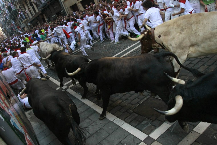 Runner sprints alongside Dolores Aguirre Ybarra fighting bulls at the Estafeta corner during the second running of the bulls of the San Fermin festival in Pamplona. (Joseba Etxaburu/Reuters photo)