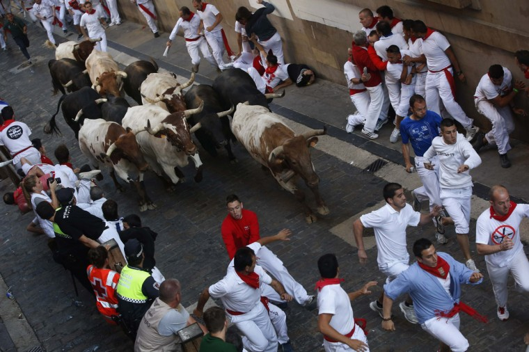 Runners sprint alongside Dolores Aguirre Ybarra fighting bulls up Santo Domingo hill during the second running of the bulls of the San Fermin festival in Pamplona. (Susana Vera/Reuters photo)