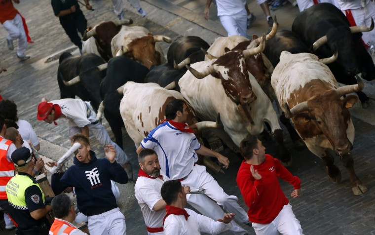 A Dolores Aguirre Ybarra fighting bull grabs the t-shirt of a runner with its horn (L, background) as they sprint up Santo Domingo hill during the second running of the bulls of the San Fermin festival in Pamplona. (Susana Vera/Reuters photo)