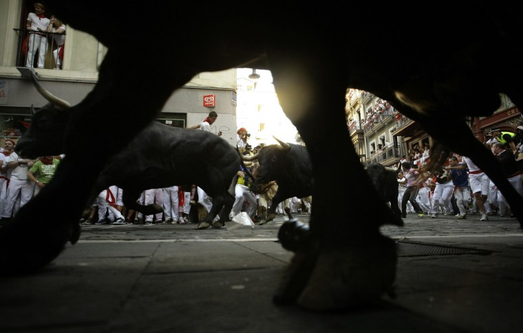 Runners sprint alongside Dolores Aguirre Ybarra fighting bulls at the Estafeta corner during the second running of the bulls of the San Fermin festival in Pamplona. (Joseba Etxaburu/Reuters photo)